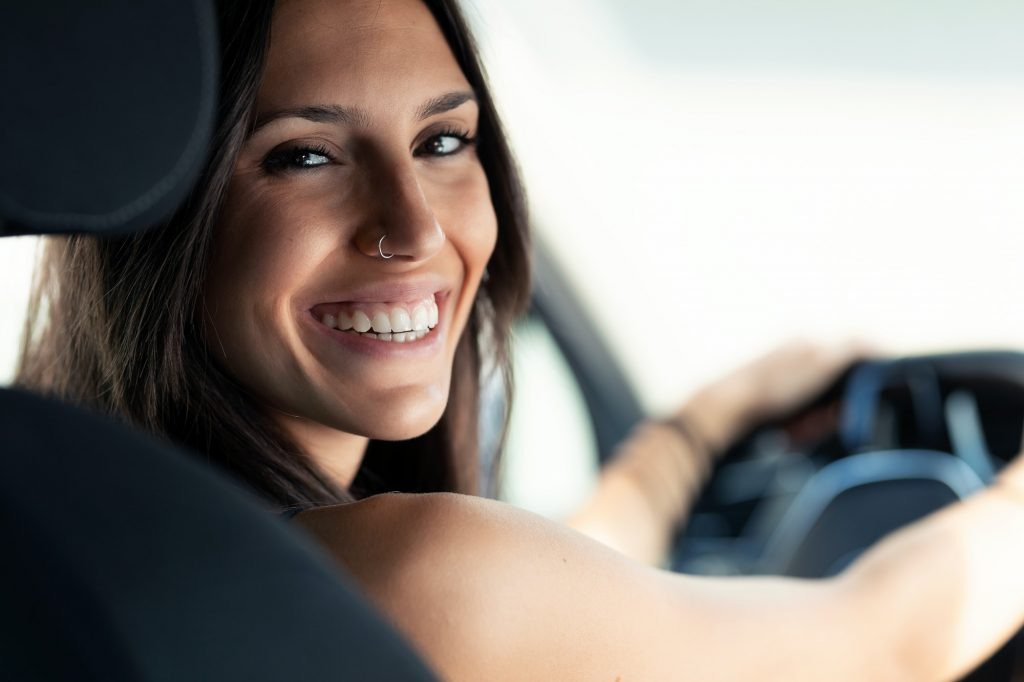 Beautiful young woman driving a car while smiling to the camera.
