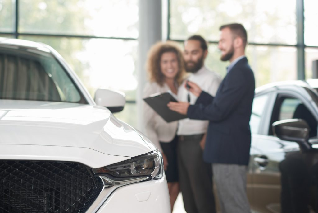 Car dealer discussing purchase of car with clients